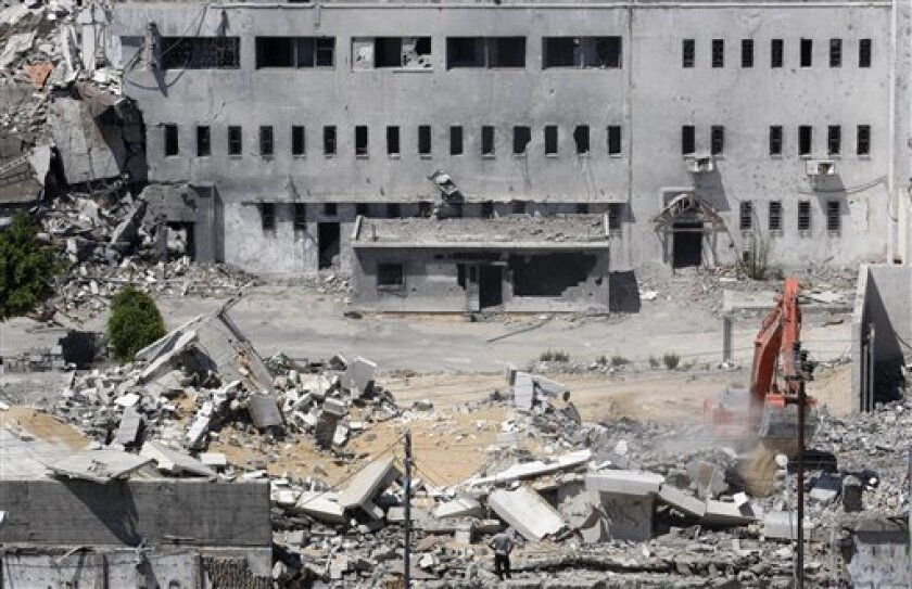 A bulldozer clears the rubble at the former Palestinian central security headquarters and prison, known as the Seraya, in Gaza City, Monday, July 13, 2009, which was destroyed in an Israeli airstrike in Dec. 2008. Removing the rubble is one of the first steps on the ground taken by the UN as part of the reconstruction plan for Gaza after the war. (AP Photo/Hatem Moussa)