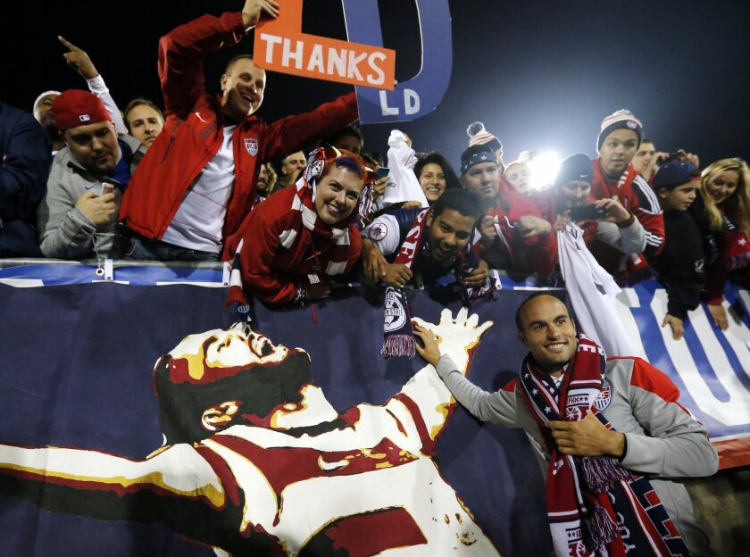 United States' Landon Donovan, bottom right, celebrates with fans after an exhibition soccer match against Ecuador in East Hartford, Conn., Friday, Oct. 10, 2014. Donovan made his last international soccer appearance Friday. (AP Photo/Elise Amendola)