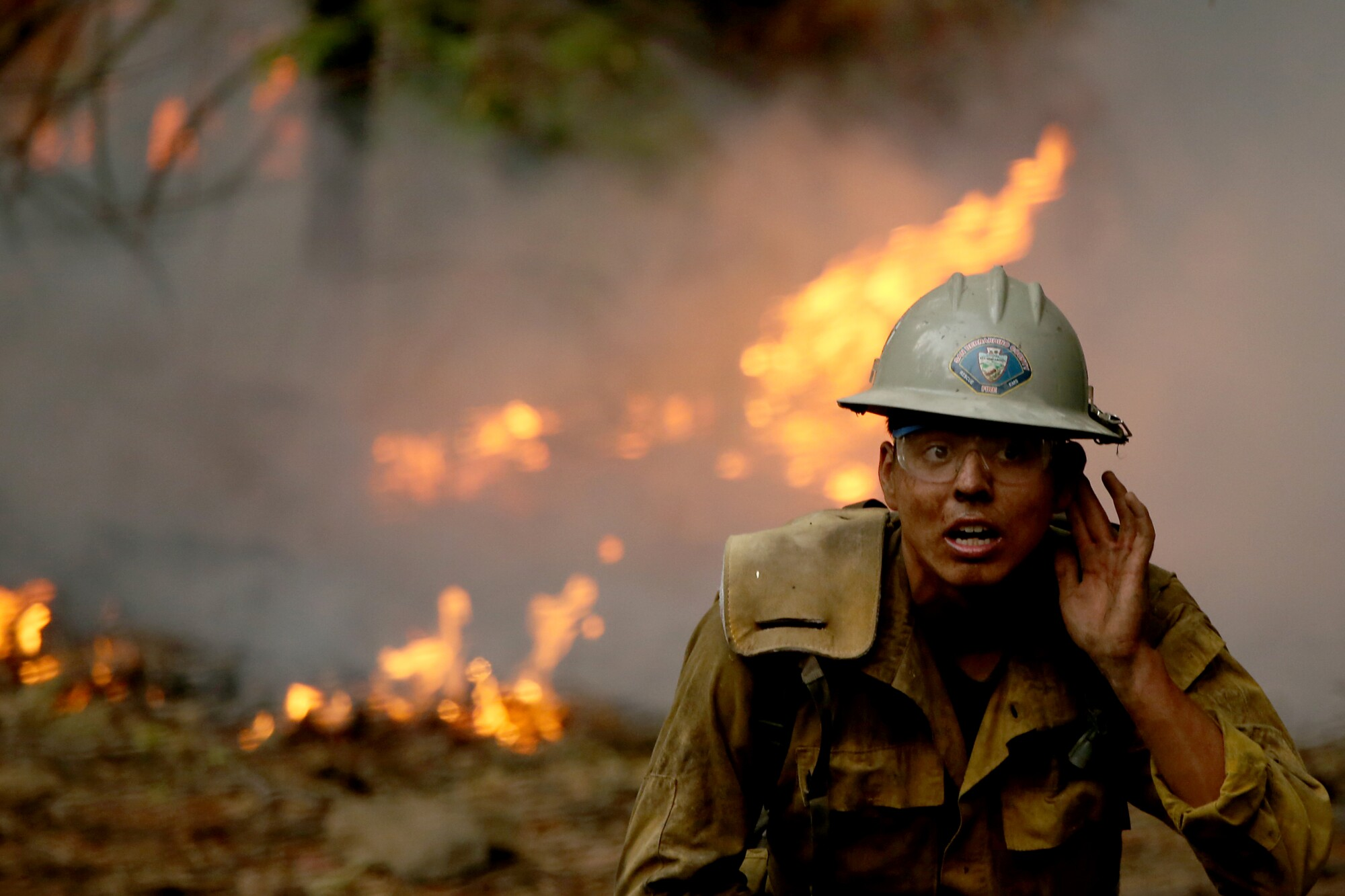 A firefighter holds a hand up to his left ear as he stands in front of flames and smoke