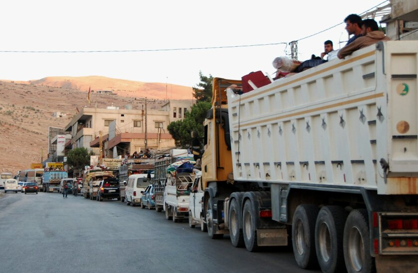 Syrian refugees flee from the Lebanese eastern town of Arsal on their way to cross back into Syria, as they ride in vehicles with their belongings at the Lebanese border crossing point of Masnaa, eastern Bekaa Valley, Lebanon, Thursday, Aug. 7, 2014. Up to 150 cars packed with Syrian refugees were seen leaving Arsal. A security official in eastern Lebanon said arrangements were made for them to cross back into Syria through the border crossing. It was not immediately clear where in Syria the refugees were going, but many may have been fleeing the violence in Arsal for areas inside their country where there has been less fighting recently. (AP Photo)