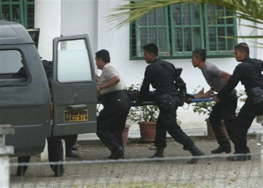 Police officers carry a colleague wounded in a raid on a suspected terrorist hideout as a part of Indonesian National Police crack down on a potential cell of the Southeast Asian terrorist network Jemaah Islamiyah in Aceh Besar, Aceh province, Thursday, March 4, 2010. Indonesian police have charged 14 suspected Islamist militants arrested in restive Aceh province with planning terrorist attacks and shot dead another, an official said Thursday. (AP Photo/Heri Juanda)