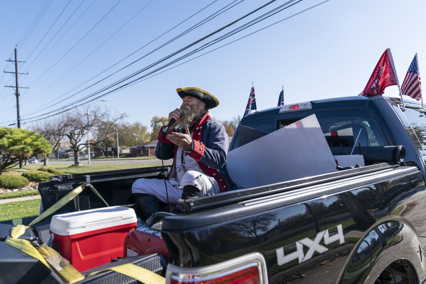 Trump supporter Matthew Woods, dressed as a Continental Army soldier, leads a Trump Train Rally on Election Day through the streets of Warren, Mich., Tuesday, Nov. 3, 2020. (AP Photo/David Goldman)