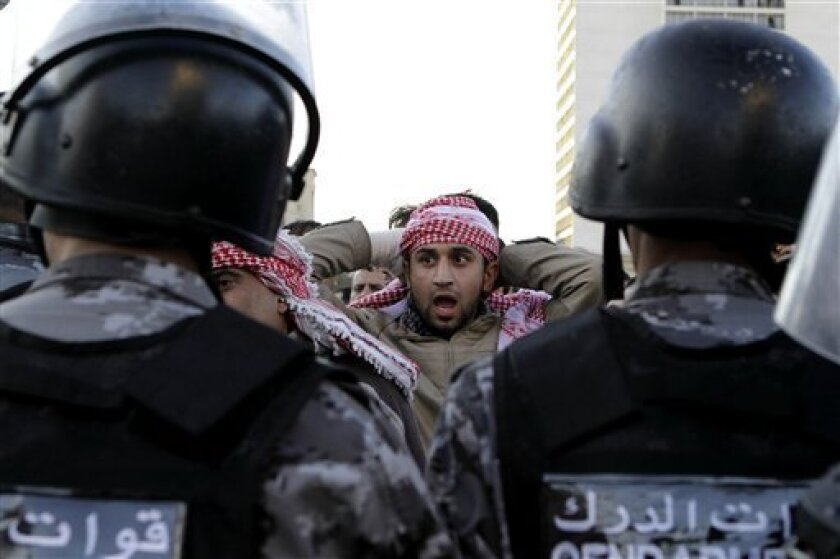 Jordanian policemen prepare to disperse protesters blocking a main road during a demonstration against a rise in fuel prices in downtown Amman, Jordan, Wednesday, Nov. 14, 2012. Hundreds of Jordanians chanted slogans against the king and threw stones at riot police as they protested in several cities for a second day Wednesday amid rising anger over fuel price hikes. (AP Photo/Raad Adayleh)