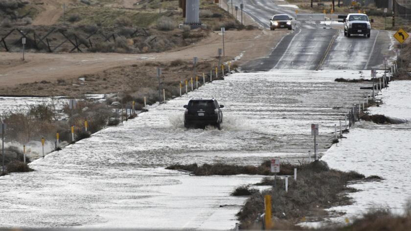 Un vehícula pasa por una inundación en Hesperia, California, los peligros todavía no han pasado y se advierte sobre el riesgo de deslaves.
