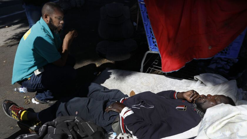 A man lies on a mattress on a sidewalk in South Los Angeles. He refused help and refused to be taken to the hospital via ambulance.