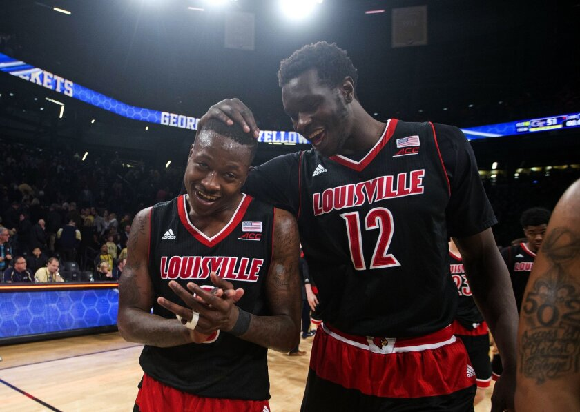 Louisville's Terry Rozier (0), left, and Mangok Mathiang (12) celebrate as they leave the court after defeating Georgia Tech 52-51 in an NCAA college basketball game Monday, Feb. 23, 2015, in Atlanta. (AP Photo/John Bazemore)