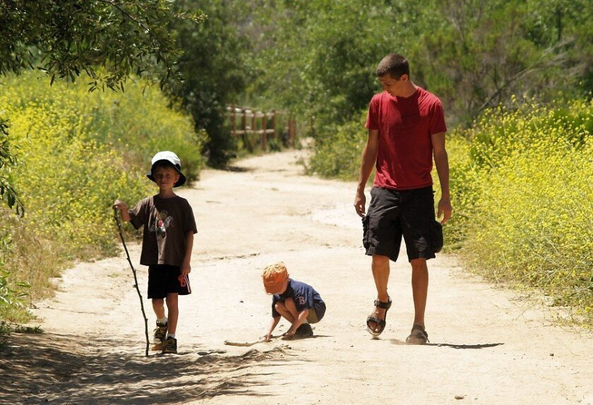 Matt Cornell, with sons Chase, 3, and Dexter, 7, hikes along the Rose Canyon trail. (Wendy Fry)