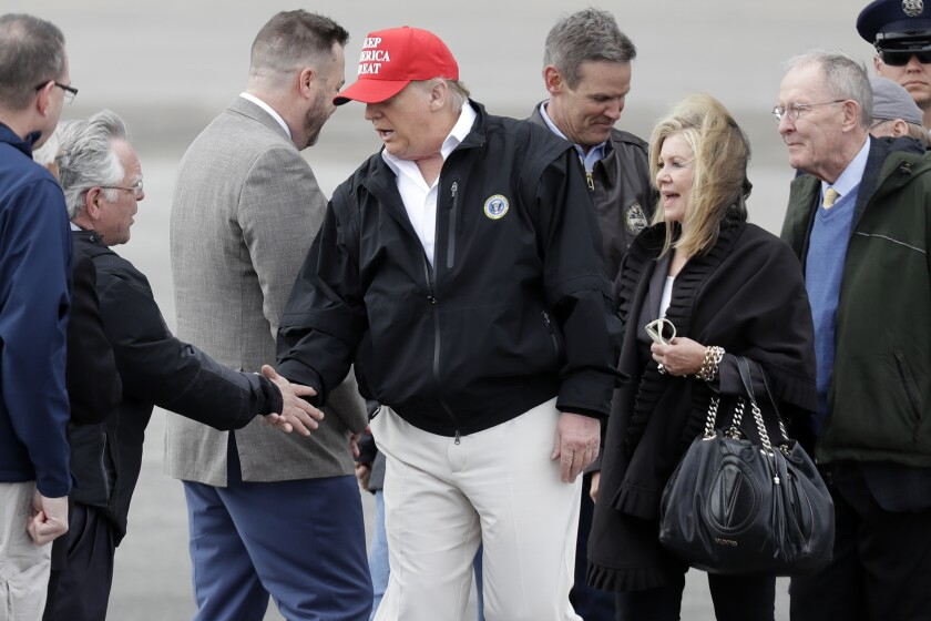 President Donald Trump is greeted by Nashville Mayor John Cooper, second from left, Friday, March 6, 2020, in Nashville, Tenn. Trump is in Tennessee to view tornado damage. (AP Photo/Mark Humphrey)
