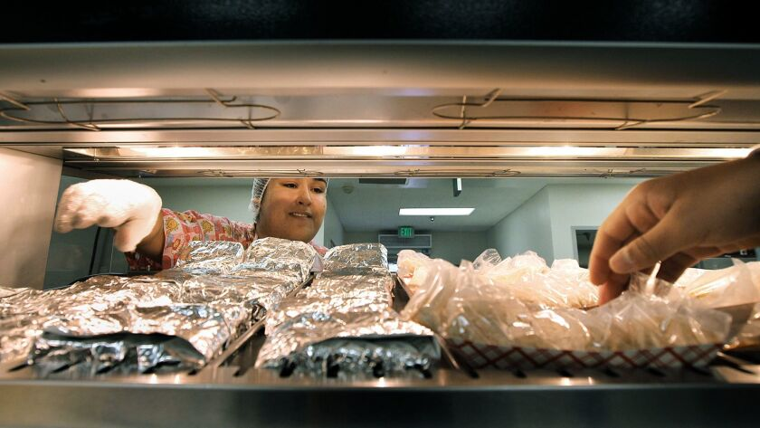 LOS ANGELES-CA-FEBRUARY 26, 2014: Kitchen worker Andrea Jimenez, left, keeps the food stocked as a s