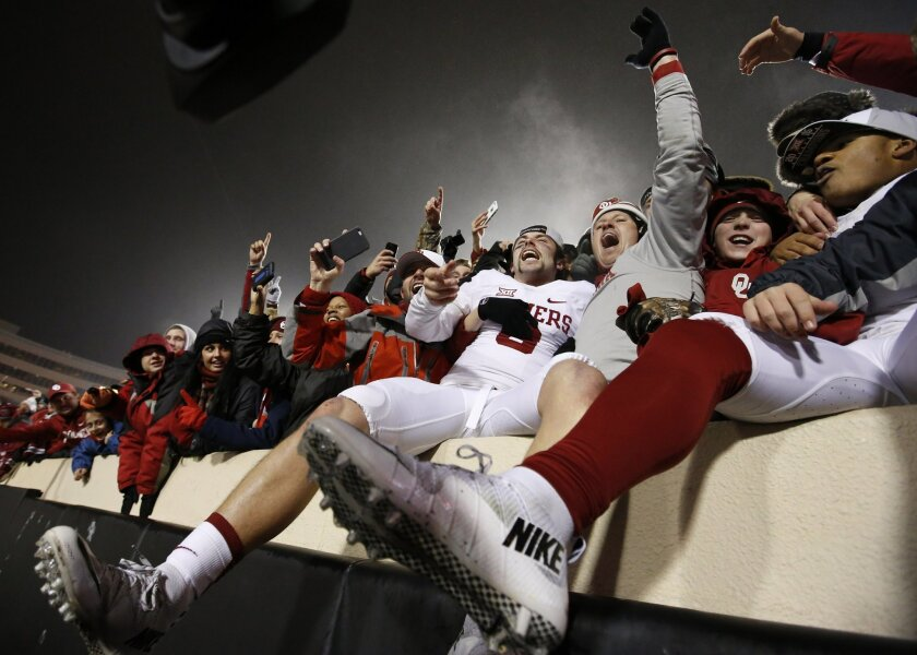 Oklahoma quarterback Baker Mayfield, center, celebrates with fans following an NCAA college football game against Oklahoma State in Stillwater, Okla., Saturday, Nov. 28, 2015. Oklahoma won 58-23. (AP Photo/Sue Ogrocki)