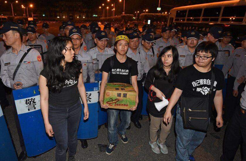 Pro-Taiwan independence protesters stand in front of riot police outside the presidential office in Taipei on April 1.