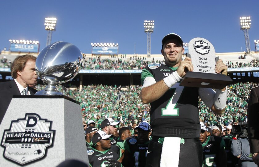 North Texas quarterback Derek Thompson (7) holds the Most Valuable Player trophy aloft after their 36-14 win over UNLV in the Heart of Dallas NCAA college football game, Wednesday, Jan. 1, 2014, in Dallas. (AP Photo/Mike Stone)