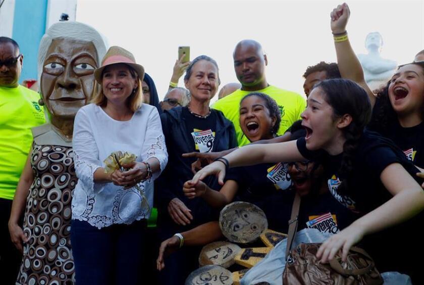 La alcaldesa de San Juan Carmen Yulín Cruz (2i), la teatrera Maritza Pérez Otero (3i) y el grupo de teatro Jóvenes del 98 (d), hacen el corte de cinta que da inicio hoy, jueves 19 de enero de 2017, a las Fiestas de la Calle San Sebastián, con la tradicional comparsa a ritmo de plena, en San Juan (Puerto Rico). EFE