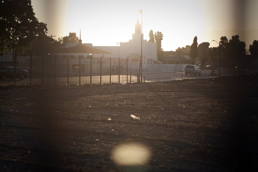 Across from the Bethlehem Church of God, a fence borders most of a vacant lot slated for redevelopment as Marlton Square at Marlton Avenue and Santa Rosalia Drive in Los Angeles.
