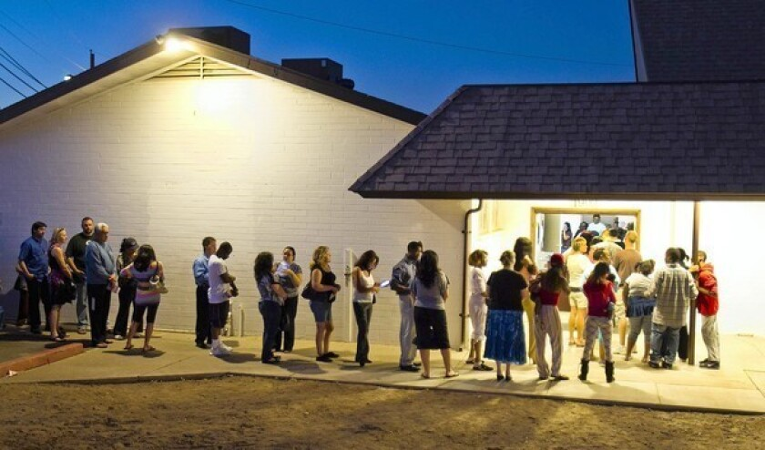 People wait in line to vote in Phoenix in November. The U.S. Supreme Court has struck down an Arizona law requiring people who register to vote to show proof of citizenship.