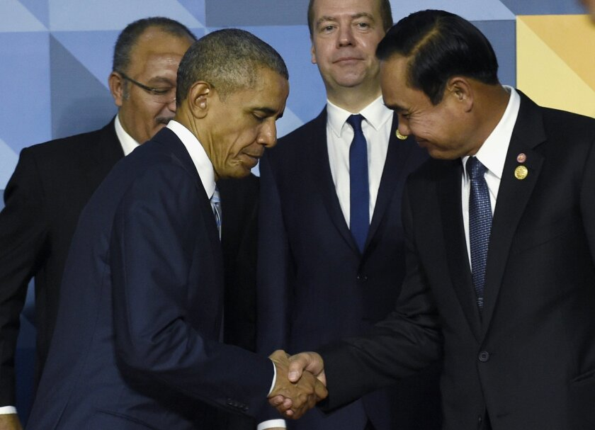 FILE - In this Nov. 19, 2015 file photo, President Barack Obama shakes hands with Thailand's Prime Minister Prayuth Chan-ocha in Manila, Philippines. When President Barack Obama welcomes Southeast Asian leaders for a shirt-sleeves summit in California this week, he'll have some interesting dining c
