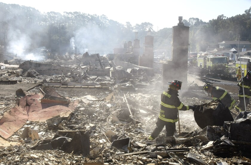 In this file photo, firefighters check for hot spots in the rubble of homes along Claremont Drive in San Bruno, Calif., where a large underground natural gas pipeline exploded in 2010.