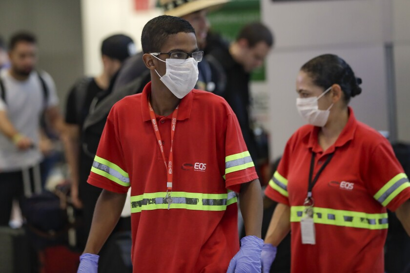 Airport employees wear masks Wednesday at the Sao Paulo International Airport in Brazil.