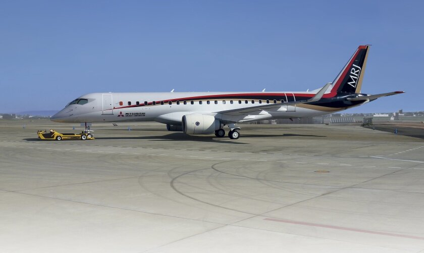 In this Wednesday, April 1, 2015 photo released by Mitsubishi Aircraft Corp., a flight test aircraft of Mitsubishi's new regional jet MRJ sits on the airstrip at Nagoya Airport in Toyoyama, central Japan. At a tightly guarded factory in central Japan, Mitsubishi, a maker of the Zero fighter planes of World War II, is launching its MRJ regional jet and aiming to fulfill Japan's long-cherished ambitions to regain status as a major aviation power. The company said Friday, April 10 that a recent decision to push back the jet's maiden flight from this spring to a few months later would not delay its commercial deliveries. (AP Photo/Mitsubishi Aircraft Corp.)