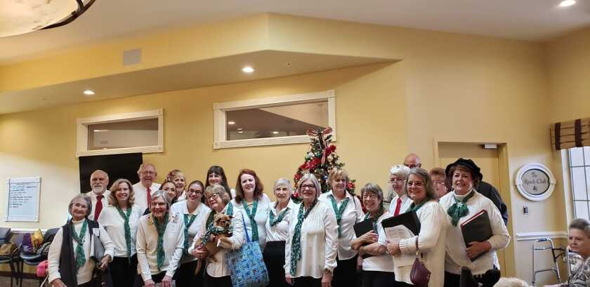 The Ramona Community Singers at a 2019 performance at a nursing home with mascot Nutmeg.