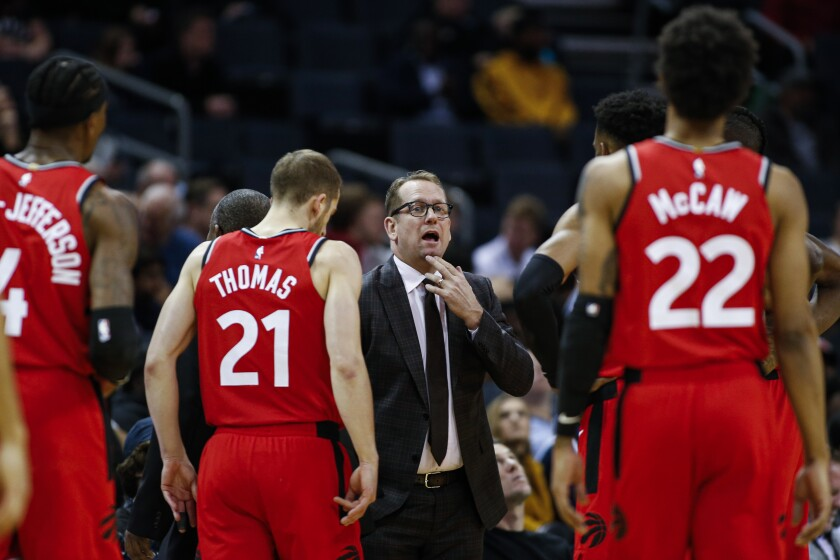 FILE - In this Jan. 8, 2020, file photo, Toronto Raptors coach Nick Nurse, center, gathers his team during a timeout in the first half of an NBA basketball game against the Charlotte Hornets in Charlotte, N.C. The Raptors have an NBA championship to defend, a very long stay at the Disney complex awaiting them and plenty of unanswered questions on how the restart of the season will work. As the NBA's lone Canadian team, there's an added complexity: The U.S. border. Nurse said Tuesday, June 9, 2020, that his team is still working through various scenarios for having workouts before heading to Disney World near Orlando, Florida along with 21 other teams next month for the restart of the season. (AP Photo/Nell Redmond, File)