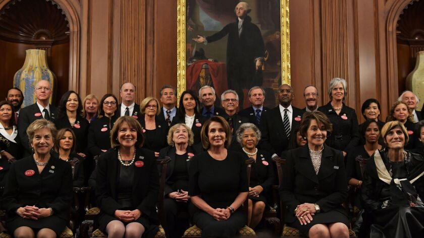 """Pelosi poses with members of Congress wearing black in support of the """"metoo"""" movement in the Rayburn Room of the US Capitol."""