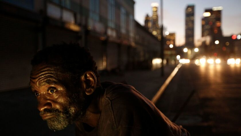 John Lee Norman, who is homeless, leans on his shopping cart along 4th Street in Los Angeles' skid row.