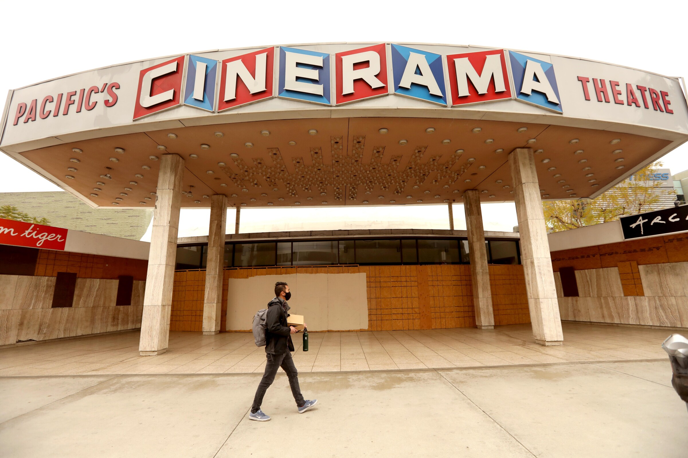 A passerby at the closed entrance to the Cinerama Dome in Hollywood.