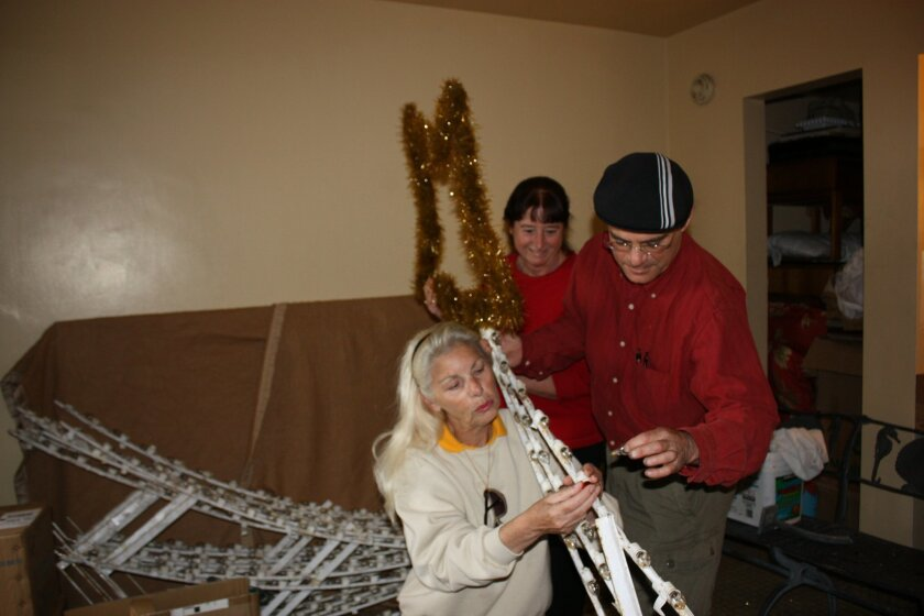 Michelle Addington, front, assists Maureen Murphy and Egon Kafka with repairing the shooting stars in 2010.  Photo: Kathy Day