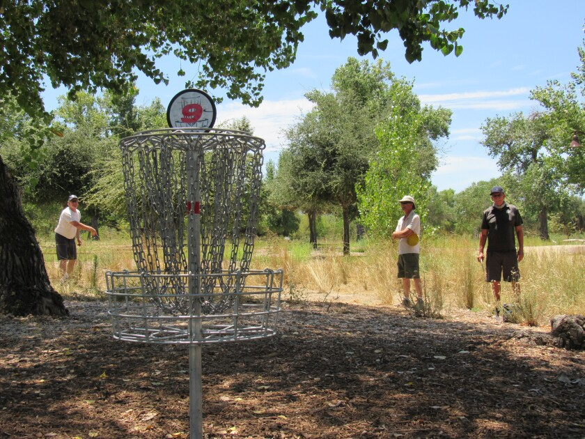 Russell Smith  (left) follows through at the Mast Park Disc Golf Course in Santee with friends John Oppenheim and Clay Young.