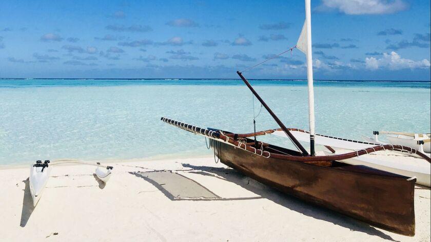 A Tahitian outrigger canoe sits on the powdery shores of Teti'aroa