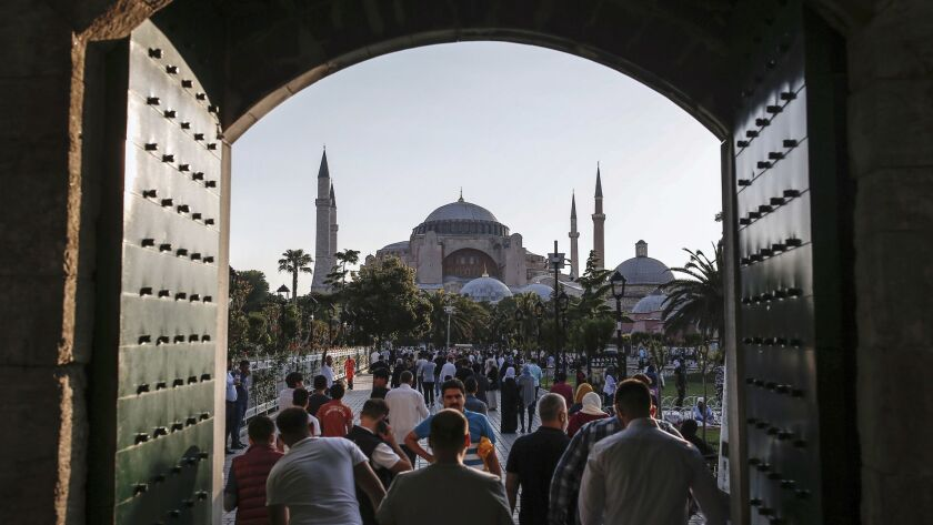 Turkish Muslims leave after Eid al-Fitr prayers at the landmark Sultan Ahmed Mosque, or Blue Mosque, in Istanbul, on June 25, 2017. The Hagia Sophia Museum, another landmark of the city, is seen in the background.
