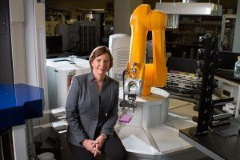 Dr. Kristiina Vuori with one of the drug screening robots in Sanford-Burnham's Conrad Prebys Center for Chemical Genomics. Courtesy photo