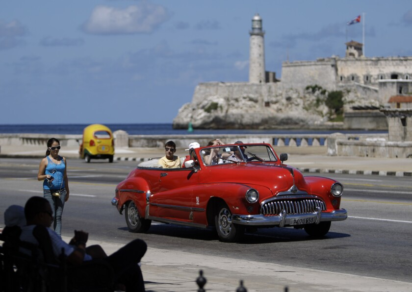 Tourists ride in a classic American car on the Malecon in Havana, Cuba.