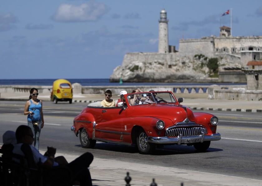 Tourists ride in a classic American car on the Malecon in Havana, Cuba.