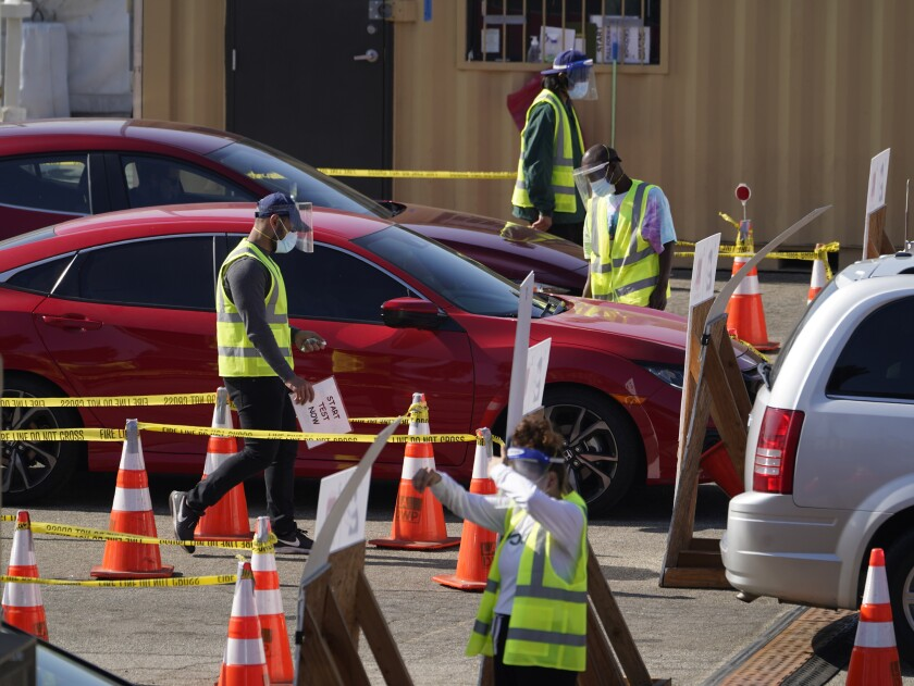Motorists wait in line to take a coronavirus test in a parking lot at Dodger Stadium in Los Angeles on Thursday, Nov. 19, 2020. (AP Photo/Damian Dovarganes)