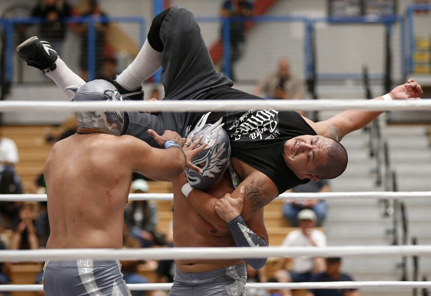 Lil Cholo, top, get thrown by Phoenix Star as partner Zokre, left, moves in during a lucha libre match at Expo Lucha at Harry West Gymnasium at San Diego City College on August 18, 2019. The three-day event featured live wrestling, along with meet and greets and vendor booth.