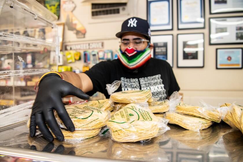 While wearing a mask and gloves, Sara's Market co-owner Steven Valdez sorts tortillas.