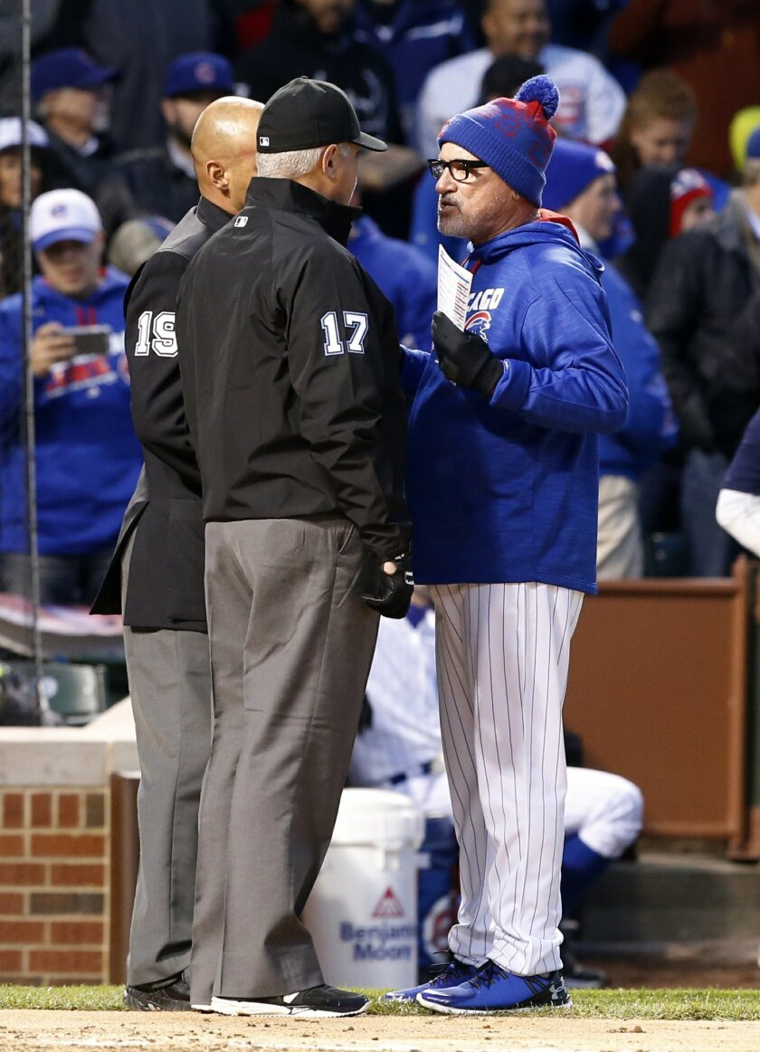 Chicago Cubs manager Joe Maddon, right, argues with home plate umpire Vic Carapazza and first base umpire John Hirschbeck after Dexter Fowler ejected by home plate umpire Vic Carapazza after the third inning of a baseball game against the Washington Nationals, Thursday, May 5, 2016, in Chicago. (AP