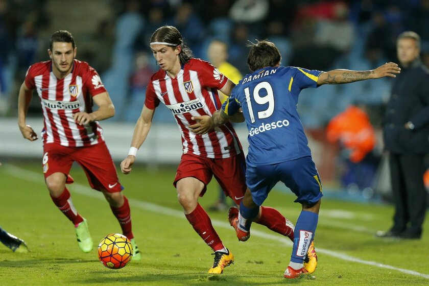 Atletico's Filipe Luis, center, duels for the ball with Getafe's Damian during a Spanish La Liga soccer match between Atletico de Madrid and Getafe at the Coliseum Alfonso Perez stadium in Getafe, Spain, Sunday, Feb. 14, 2016. (AP Photo/Daniel Ochoa de Olza)