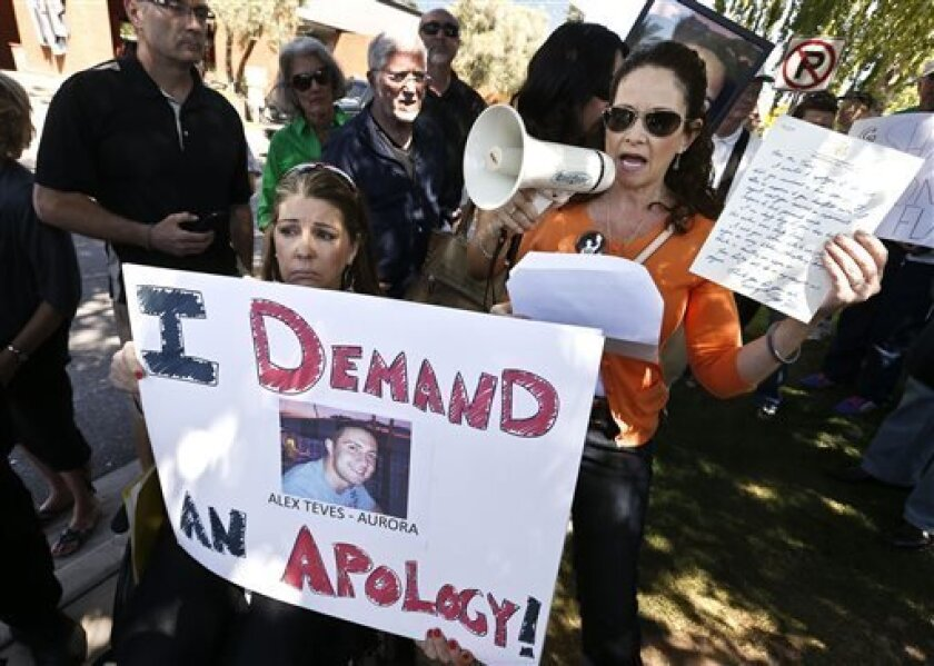 Caren Teves, right, whose son was killed in the Aurora, Colo., mass shooting, speaks as she holds up a handwritten letter to her from Sen. Jeff Flake, R-Ariz., as Jennifer Longdon, left, a shooting victim who was left paralyzed, holds up a protest sign as they join more than 50 anti-gun activists rallying outside Flake's office, Friday, April 19, 2013, in Phoenix. Flake said Friday he wants Congress to expand background checks for firearm buyers, despite his recent vote against the Senate's bip