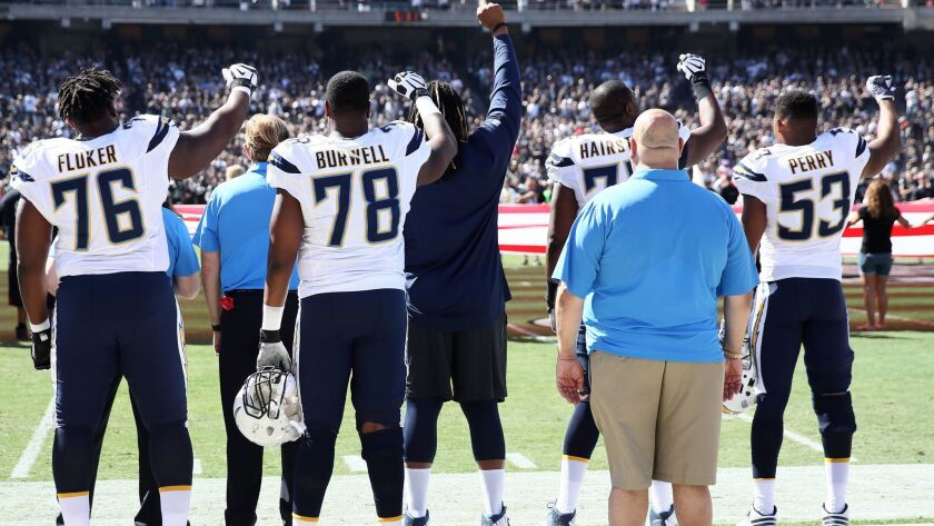 D.J. Fluker (76) Tyreek Burwell (78), Chris Hairston (75) and Joshua Perry (53) of the Chargers raise fists in protest during the national anthem prior to a game vs. the Raiders on Oct. 9.