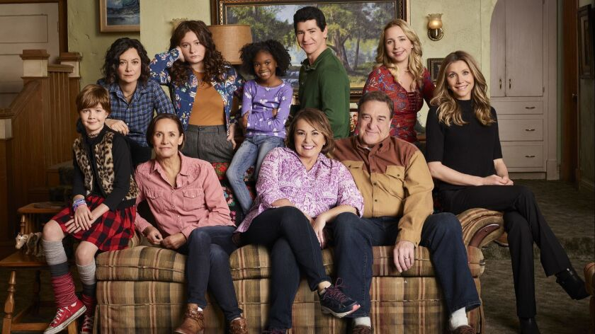 "Back on the couch, the cast of ""Roseanne."" From left: Ames McNamara, Sara Gilbert, Laurie Metcalf, Emma Kenney, Jayden Rey, Roseanne Barr, Michael Fishman, John Goodman, Lecy Goranson and Sarah Chalke as Andrea."