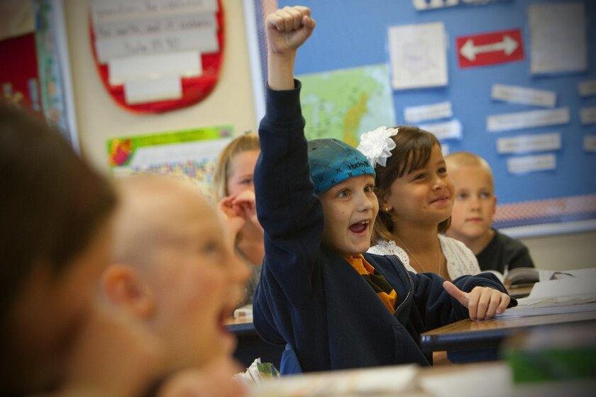 A student raises his hand during an English lesson in a second-grade class at Maranatha Christian Schools.