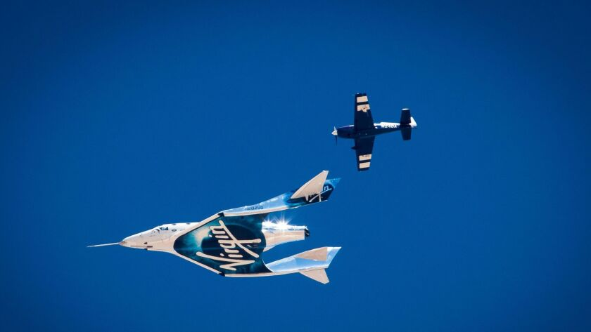 Virgin Galactic's VSS Unity space plane glides while being monitored by a chase plane during its test flight over Mojave.