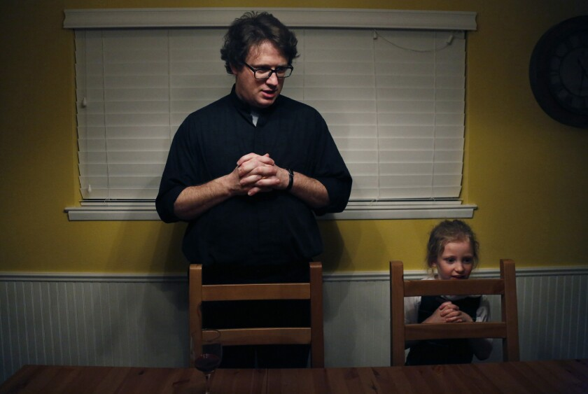 In this Feb. 7, 2020, photo, converted Catholic Priest Joshua Whitfield, left, his daughter Zoe-Catherine, 5, and the rest of his family stand behind their chairs to say grace before dinner in north Dallas. (AP Photo/Jessie Wardarski)