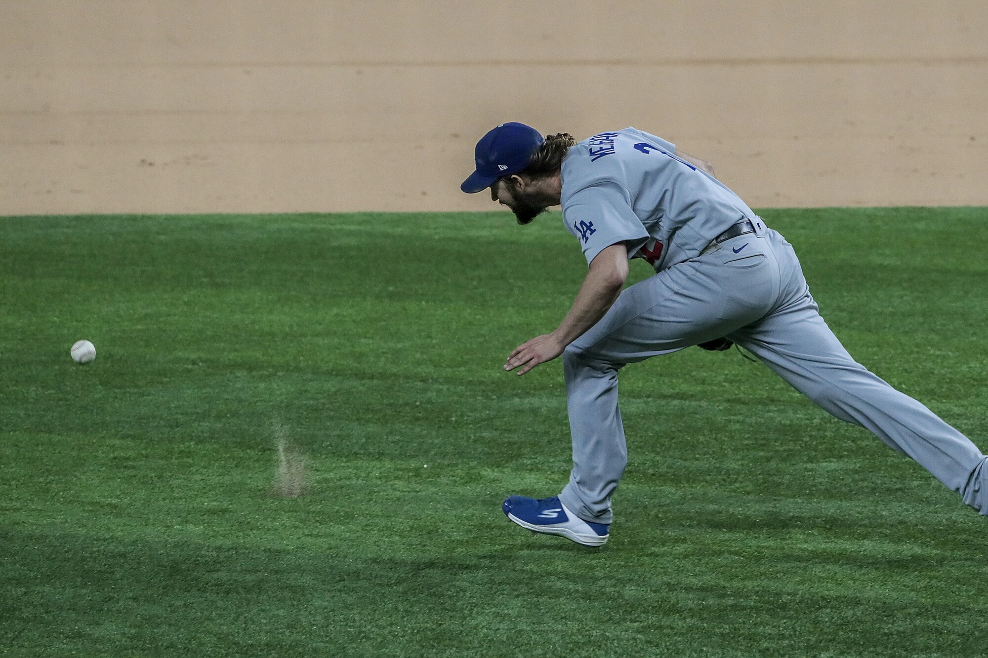 Dodgers starter Clayton Kershaw chases a grounder hit by Atlanta's Ronald Acuna Jr.