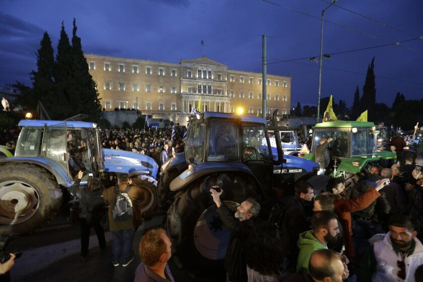 Farmers drive their tractors during a protest in front of the Greek parliament in Athens, Friday, Feb. 12, 2016. Farmers from across Greece gather in Athens for a two-day protest against the government and its plans to impose new tax hikes and pension charges. Bailout lenders are demanding that Gre