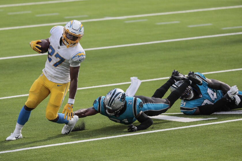 Chargers running back Joshua Kelley (27) slips past the Panthers'  Jeremy Chinn (21) and  Efe Obada.