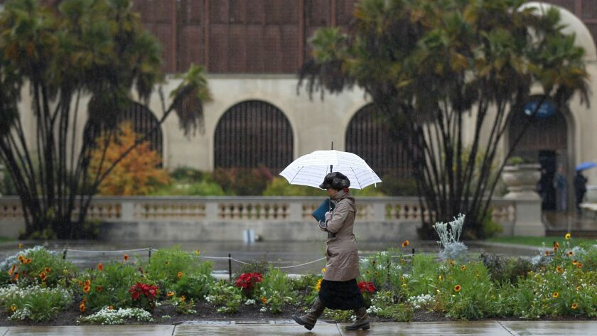 A woman walks through Balboa Park as the rain came down on Monday. More rain is expected Wednesday morning and Thursday.